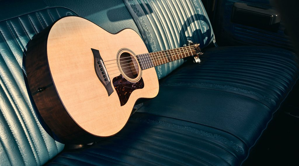 Taylor GT guitar on leather car seat in sunlight