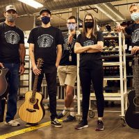 Taylor Guitars employees wearing masks inside acoustic guitar factory