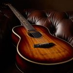Taylor GT K21e acoustic guitar lying on leather couch